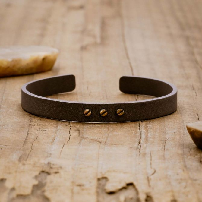 Resiliency black cuff bracelet handcrafted in sterling silver and sandblasted to a matte black finish with your choice of up to 6 bronze rivets