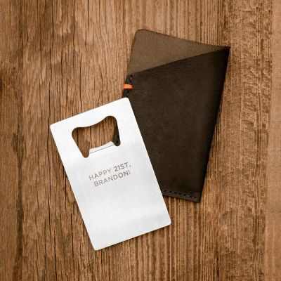 Personalized Trailblazer Bottle Opener and Leather Wallet on wood background